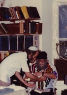 Rabbi Arthur Waskow being handed a baby by an unidentified man, pt. 4 of 4.