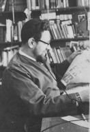 Rabbi Zalman Schachter in his office reading the newspaper while talking on the telephone, pt. 4 of 7.