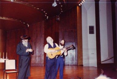 Rabbi Zalman Schachter, Rabbi Shlomo Carlebach, and David Zeller performing on stage at the Transpersonal Association Conference, 1982.