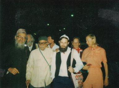 Rabbi Zalman Schachter, Paul Horn, Rabbi Shlomo Carlebach, Rabbi David Zeller, and two unidentified women with an elder of the Bombay Jewish community.