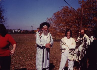 Rabbi Zalman Schachter-Shalomi with a baby carrier, two unidentified women, and one unidentified man at a Simhat Torah retreat in 1981 (5742), pt. 1 of 3.