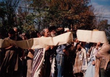 Rabbi Zalman Schachter-Shalomi reading from an unfurled Torah scroll at a Simhat Torah celebration.