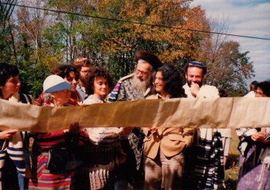 Rabbi Zalman Schachter-Shalomi with a group of others at Fellowship House Farm reading from unfurled Torah scroll.