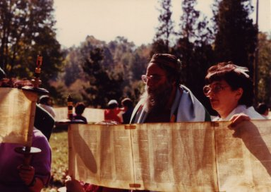 Rabbi Arthur Waskow and an unidentified woman in front of an unrolled Torah scroll, pt. 2 of 4.