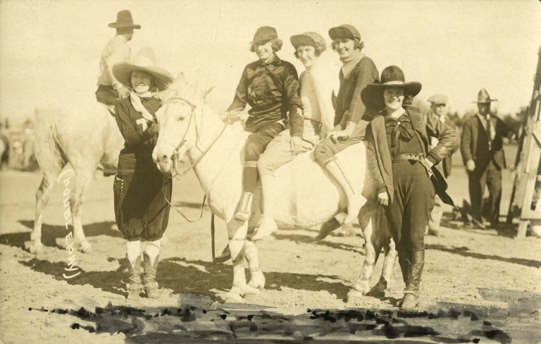 Three women rodeo performers on a horse with two others standing