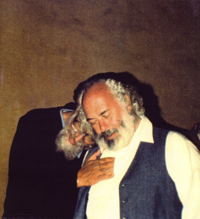 Rabbi Zaman Schachter-Shalomi with his head on Rabbi Shlomo Carlebach's shoulder, and hand on his heart in Berkeley, California, 1988.
