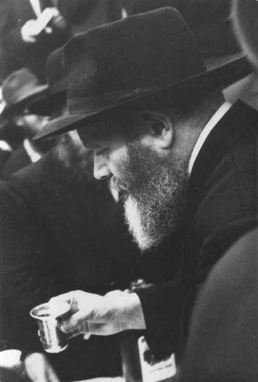 """Rabbi Menachem Mendel Schneerson, the seventh Lubavitcher Rebbe, giving a """"l'hayyim"""" at a Lubavitch farbrengen at 770 Eastern Parkway, Crown Heights, Brooklyn, New York, ca. 1960."""