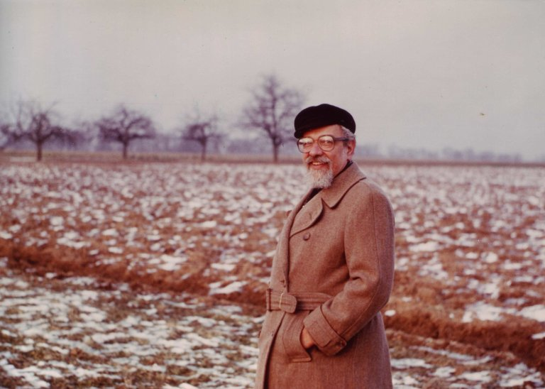 Rabbi Zalman Schachter-Shalomi out in a field in a trench-coat and fisherman's cap, ca. 1984.