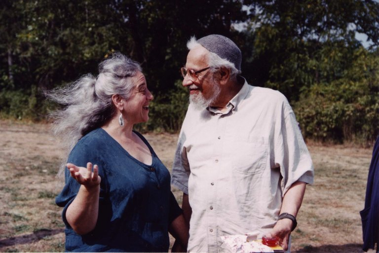 Rabbi Zalman Schachter-Shalomi outdoors in a playful conversation with his wife, Eve Ilsen, with an unwrapped present (a yo-yo) in his hand, ca. 1998.