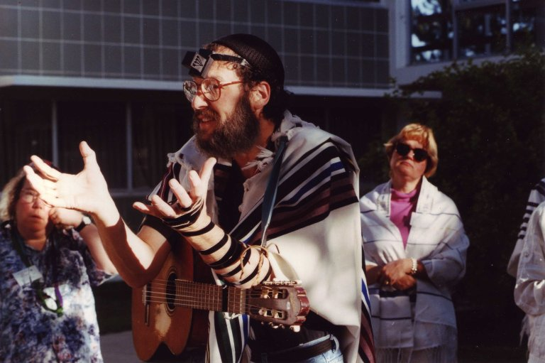 Rabbi David Zaslow in tallit and tefillin with guitar teaching at the ALEPH Kallah, 1997.