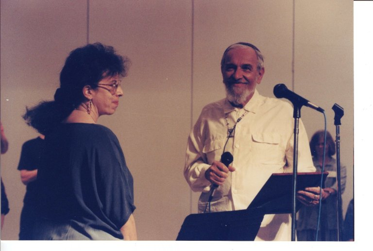 Susan Saxe and Rabbi Zalman Schachter-Shalomi on stage together, ca. 1990s.