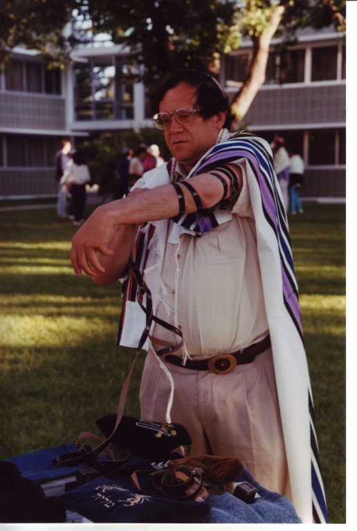 Rabbi Michael Lerner putting on t'fillin at the Kallah, 1997.