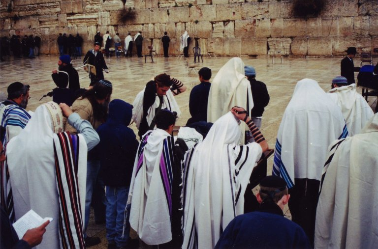 A group of Jews praying in rainbow colored tallitot that Schachter-Shalomi designed at the Kotel.