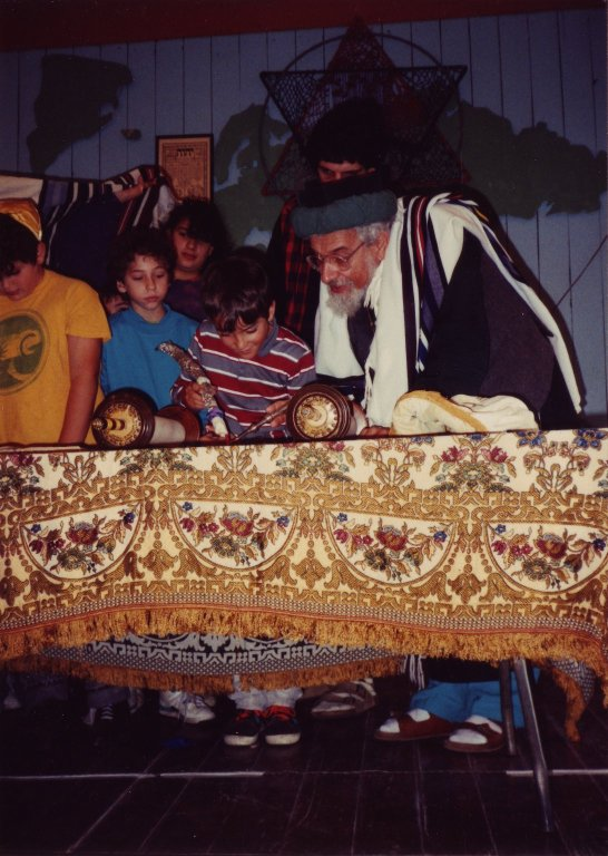 Rabbi Zalman Schachter-Shalomi helping children to read from the Torah scroll on Simhat Torah at Fellowship House Farm.
