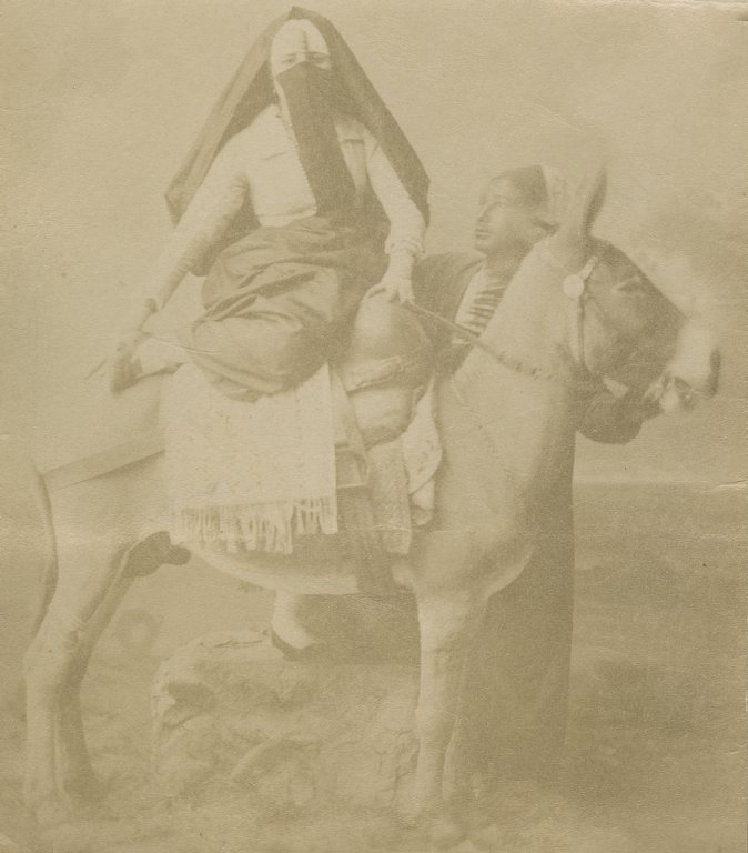 Veiled woman riding a donkey or ass.