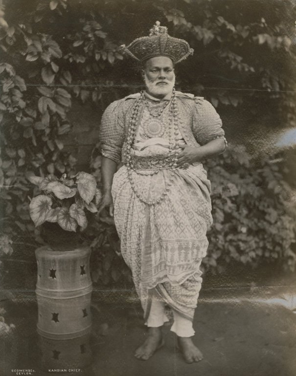 """Man (""""Kandian Chief"""") wearing dhoti, quilted jacket and a beaded necklace. Possibly Kandy, Sri Lanka."""