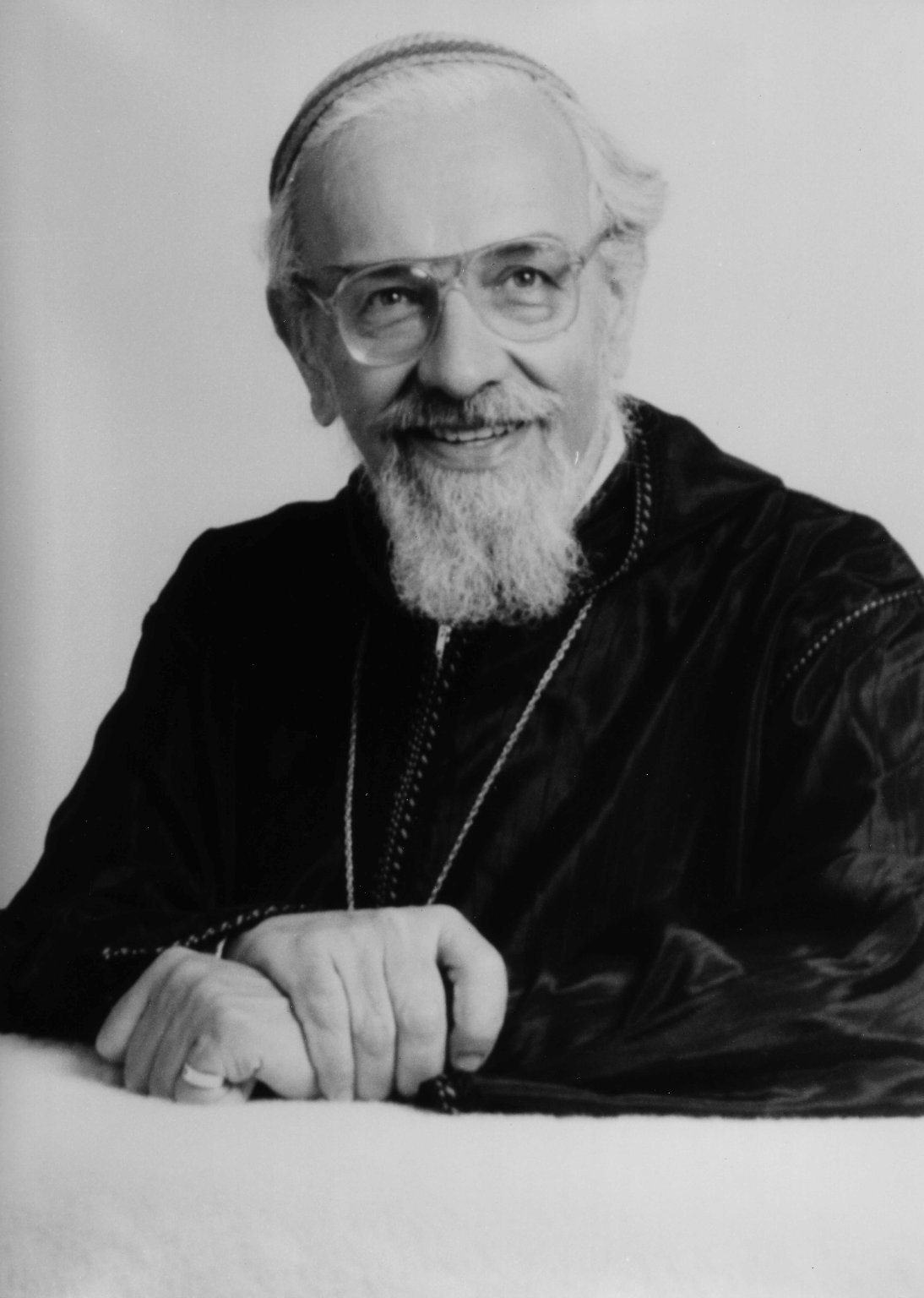 Studio portrait of Rabbi Zalman Schachter-Shalomi in a black velvet robe with embroidery, holding his own wrist, ca. 1985.