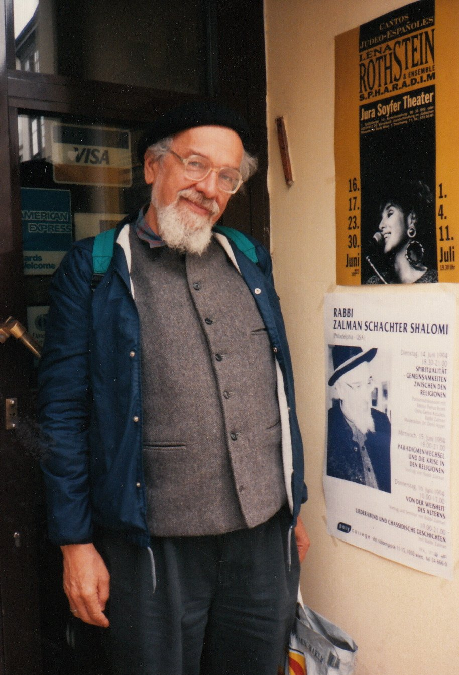 Rabbi Zalman Schachter-Shalomi standing next to a poster advertising his lecture in Vienna, Austria, June 1994.