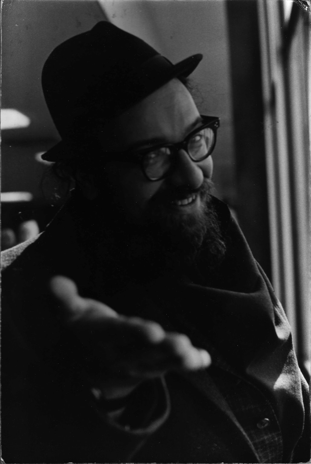 Rabbi Zalman Schachter in black hat posing playfully, extending a hand, ca. 1965.