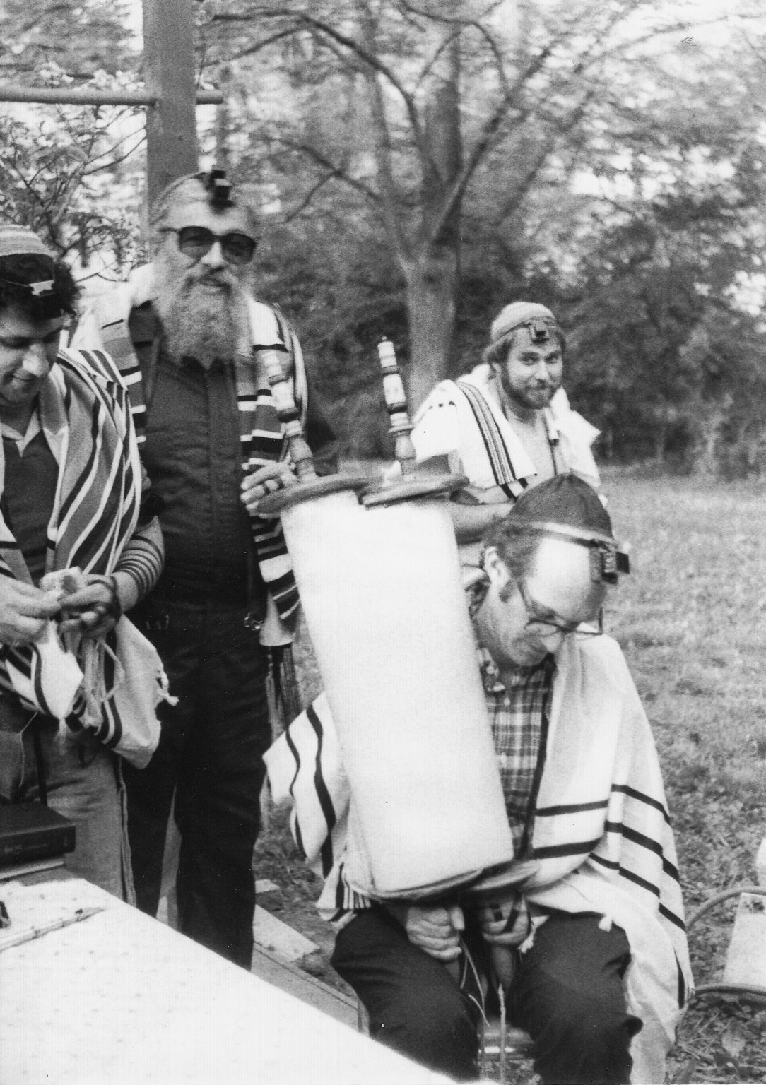Rabbi Zalman Schachter (with three unidentified men, one holding a Torah scroll) wearing Rashi and Rabbenu Tam tefillin on the same strap according to his custom at the time, 1980s.