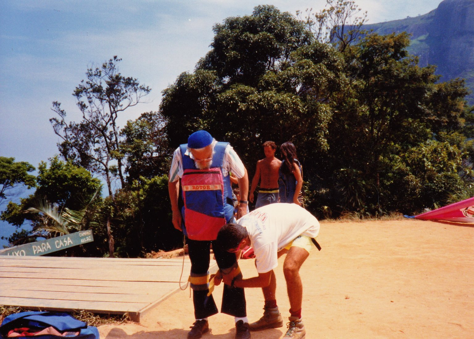 Rabbi Zalman Schachter-Shalomi getting harnassed for a hang-glider flight by the pilot, ca. 1990.