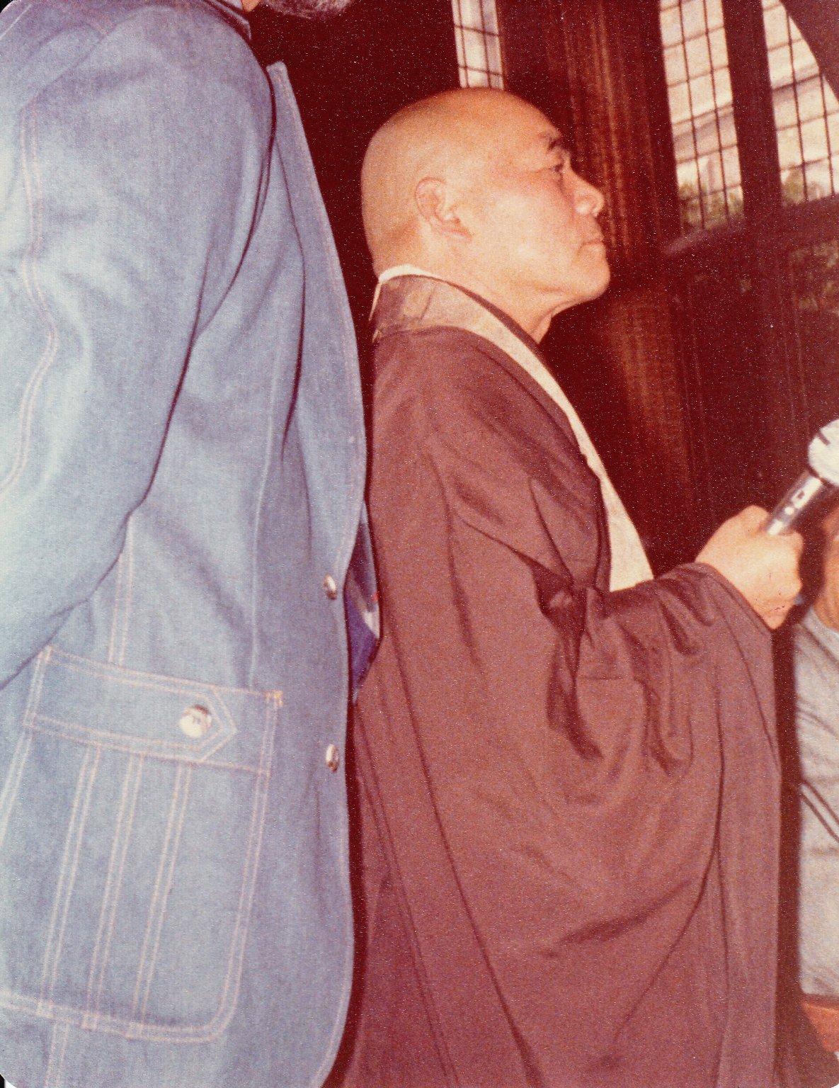 Joshu Sasaki Roshi holding a microphone.
