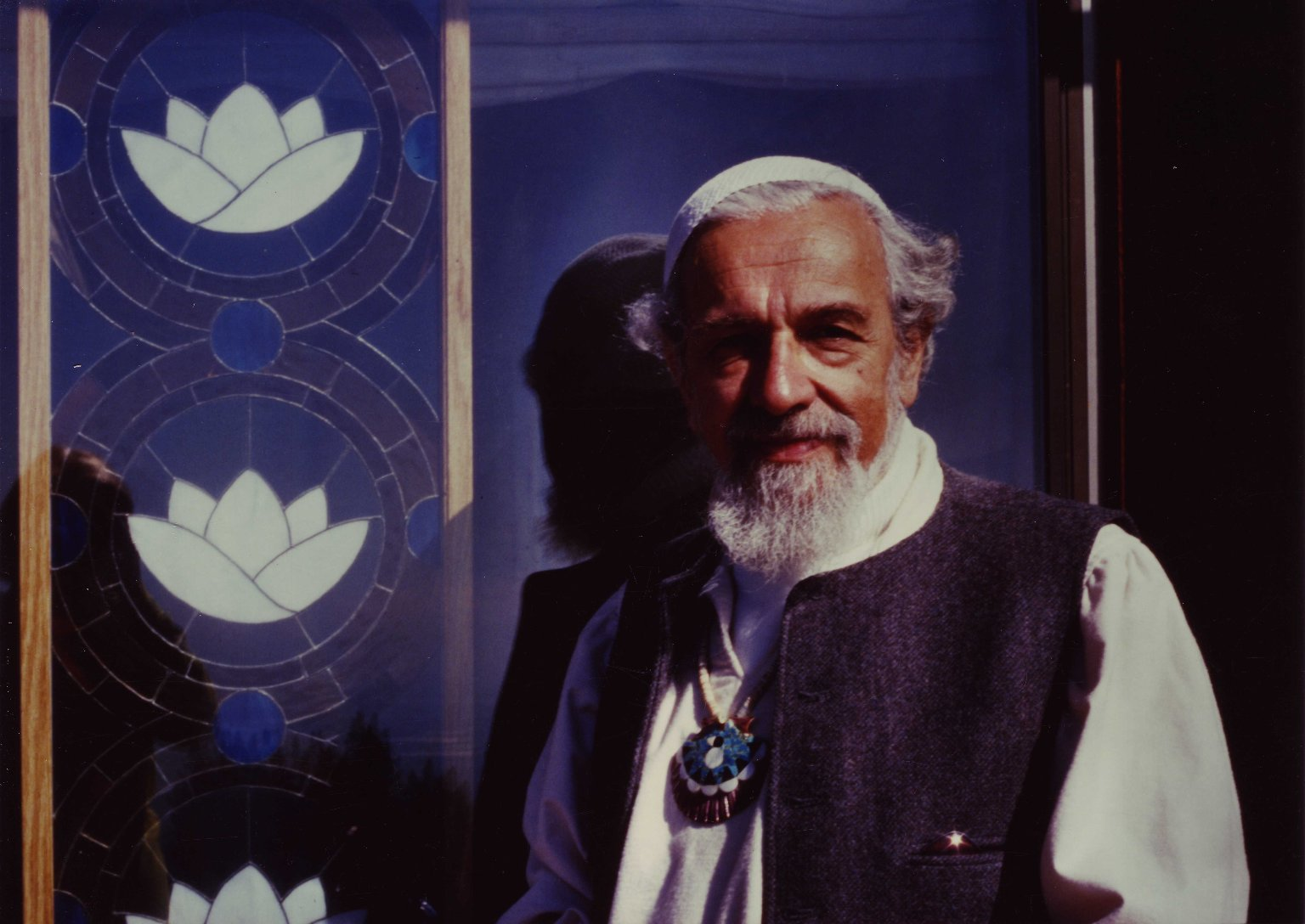 Rabbi Zalman Schachter-Shalomi standing next to stained glass lotus blossoms at the Mount Madonna Center, ca. 1999