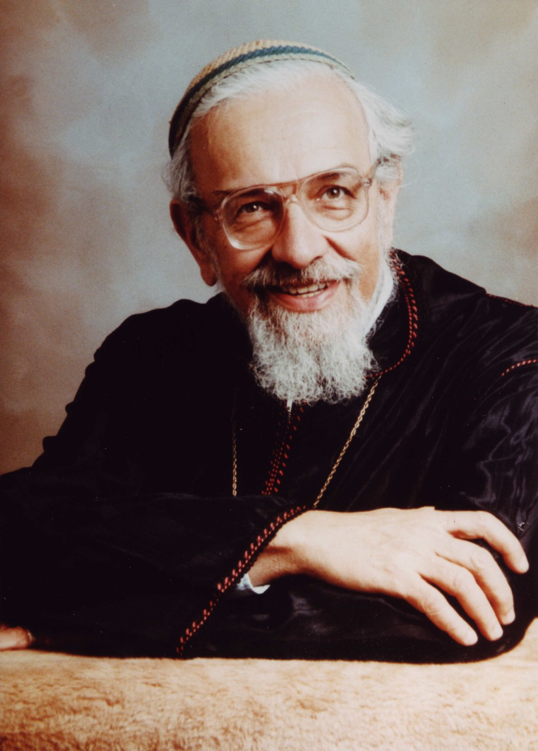 Studio portrait of Rabbi Zalman Schachter-Shalomi in a black velvet robe with orange and gold embroidery, ca. 1985.