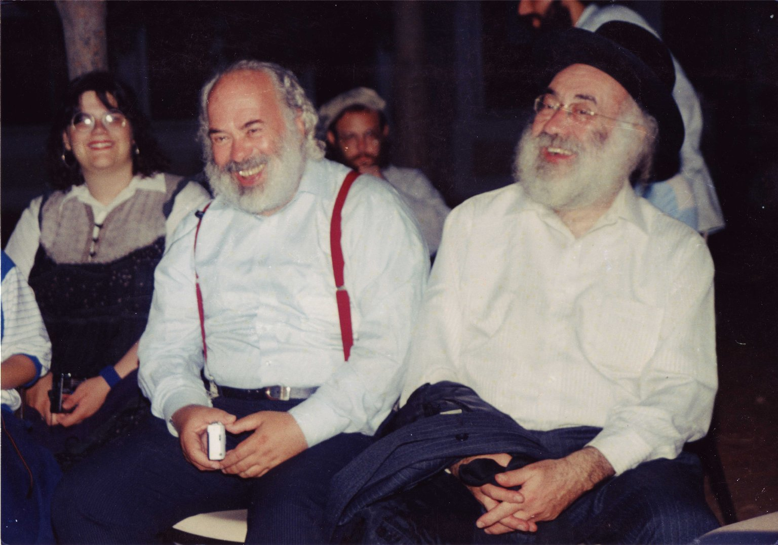 Rabbi Shlomo Carlebach (with red suspenders) and his twin brother, Rabbi Eliyah Hayyim Carlebach (in a black hat), and an unidentified woman in Israel, ca. 1985.