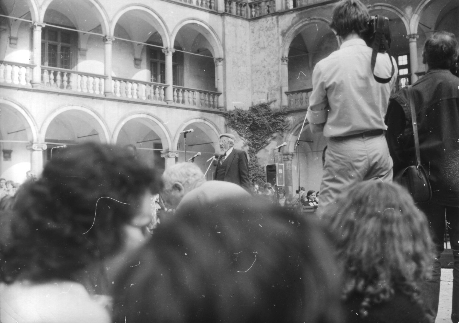 Rabbi Zalman Schachter-Shalomi speaking at the Festival of the Spirit in Krakow, Poland, with attendees and the media in the foreground, ca. 1985.