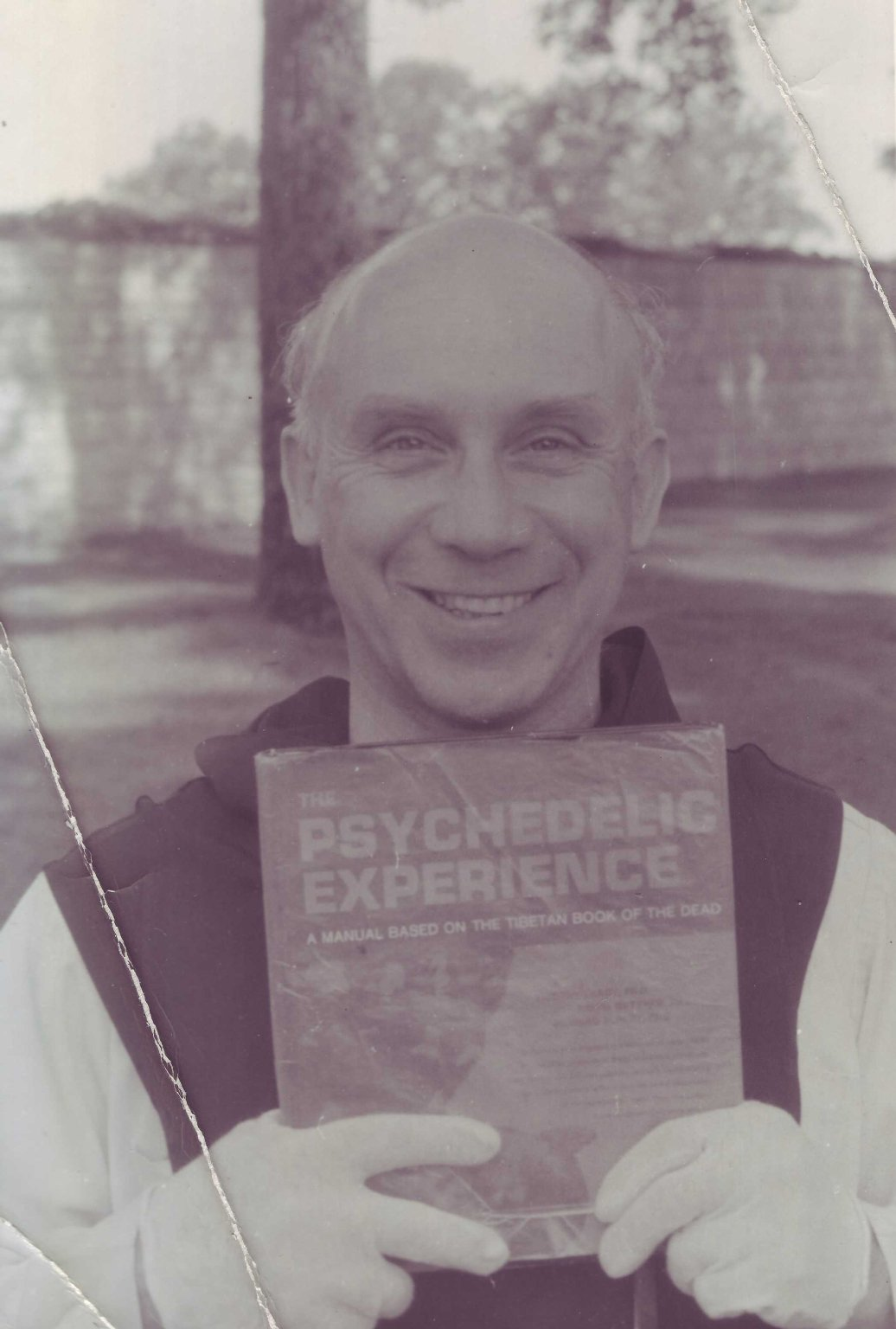 Father Thomas Merton outside of his Shangri-la hermitage, holding a copy of The Psychedelic Experience by Timothy Leary, Ralph Metzner, and Richard Alpert, given to him that day by Rabbi Zalman Schachter, ca. 1963.
