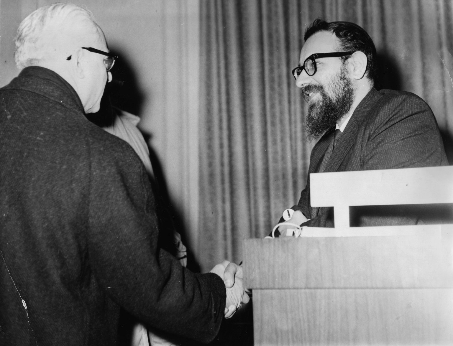 Rabbi Zalman Schachter shaking hands with someone after a Hillel Foundation talk in Pittsburg, Pennsylvania in 1962 or 63.