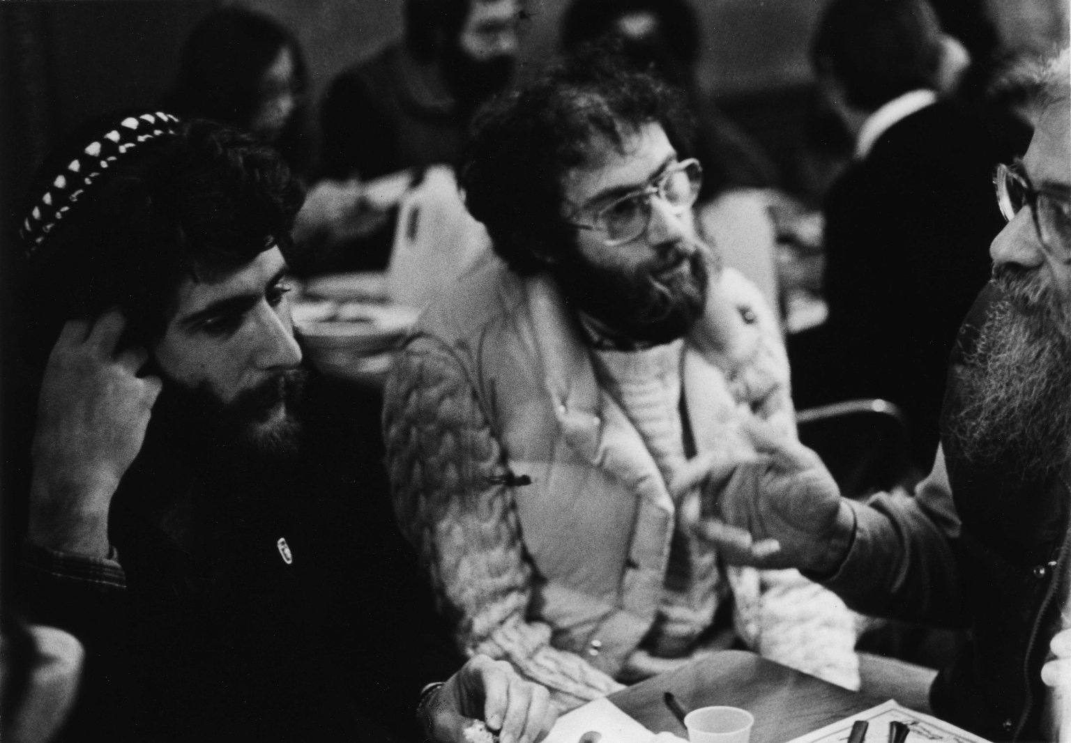 Candid photo of an unidentified man, Rabbi Lawrence Kushner, and Rabbi Zalman Schachter in conversation, ca. 1980.