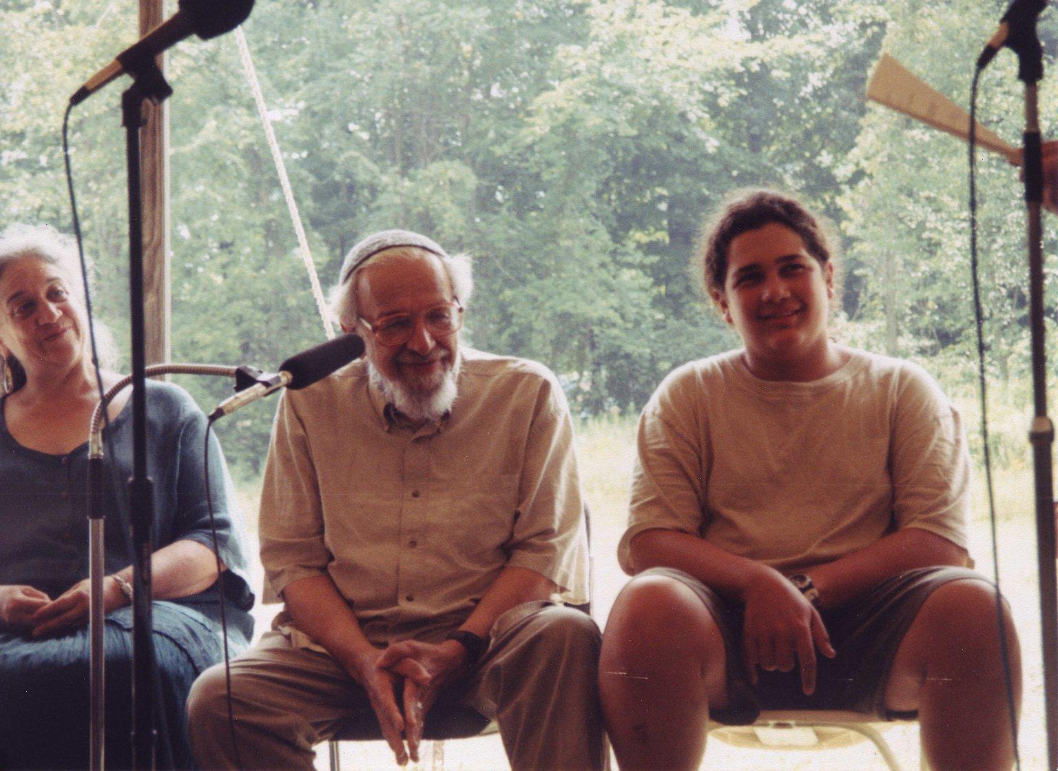 Candid photo of Eve Ilsen, Rabbi Zalman Schachter-Shalomi, and Yotam Schachter at Rabbi Zalman Schachter-Shalomi's 75th birthday celebration at Elat Chayyim, ca. 1999.