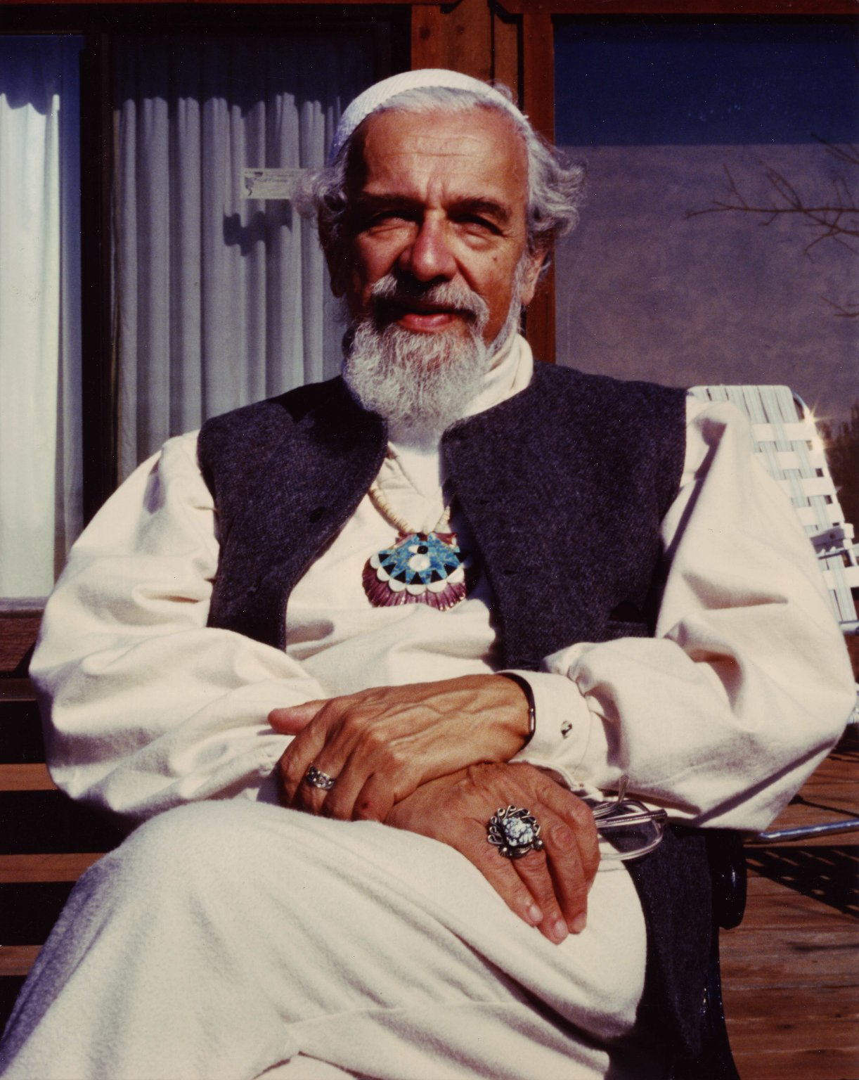 Close-up of Rabbi Zalman Schachter-Shalomi seated on a bench at the Mount Madonna Center with his hands in his lap, ca. 1999.