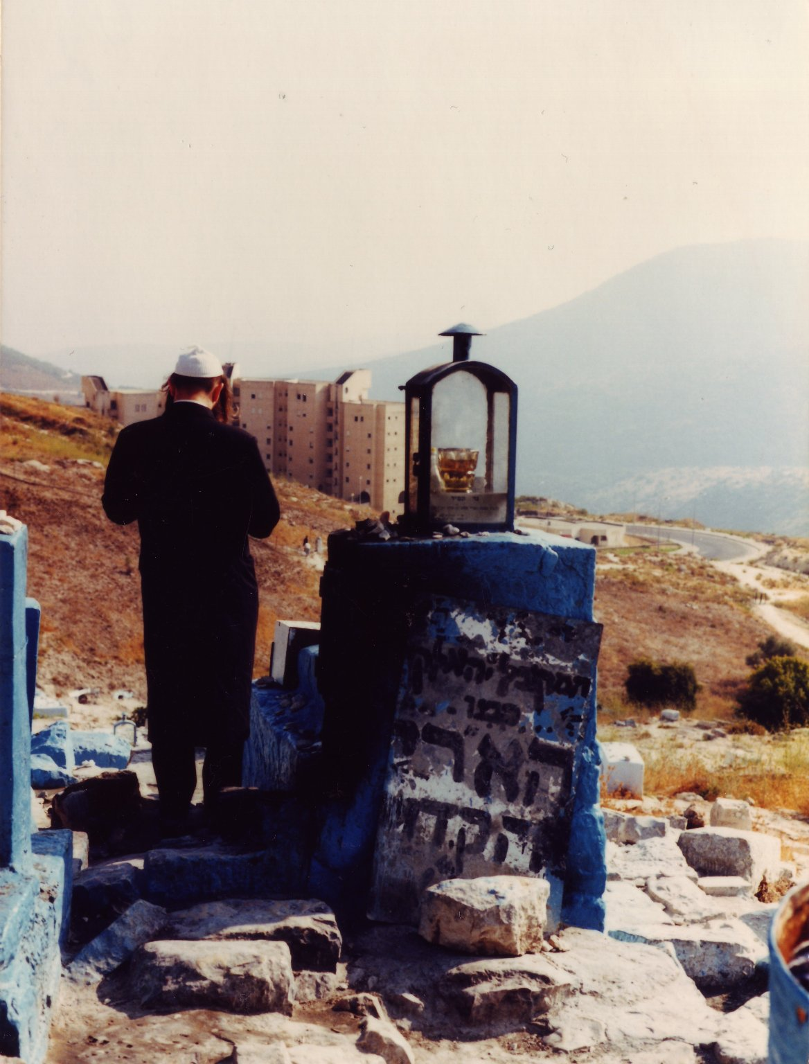 """A Hasid praying at the grave (kever) of the AR""""I, Rabbi Yitzhak Luria."""