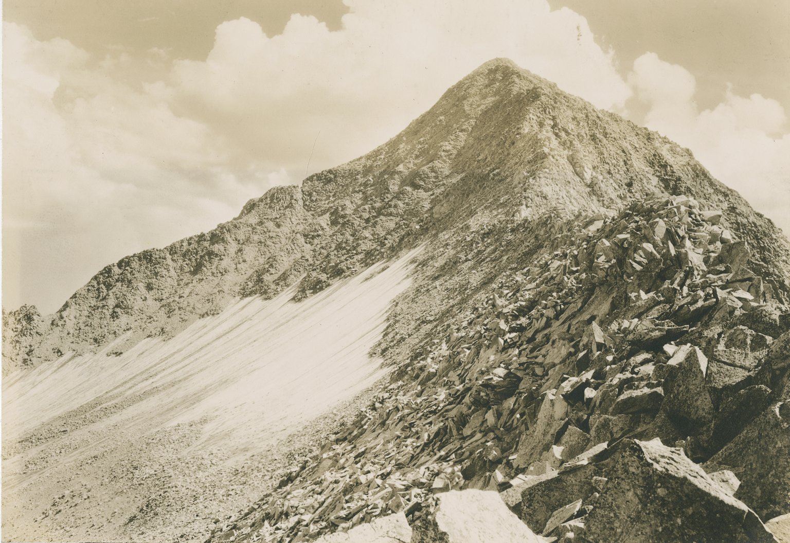 Untitled photo of mountain peak with snowfield and boulder fragments.