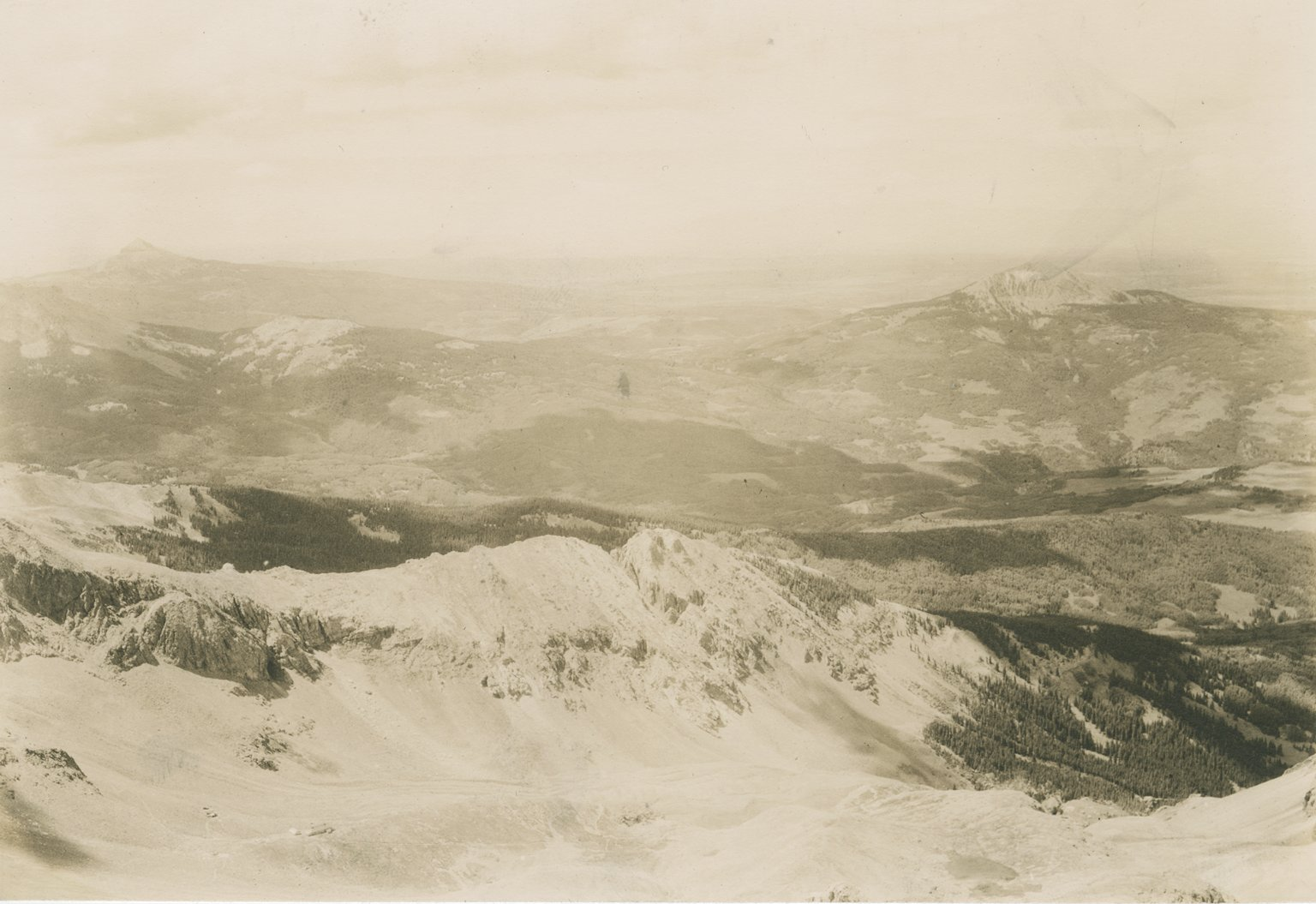 Untitled photo of mountain slope, with forested valleys and several distant peaks.