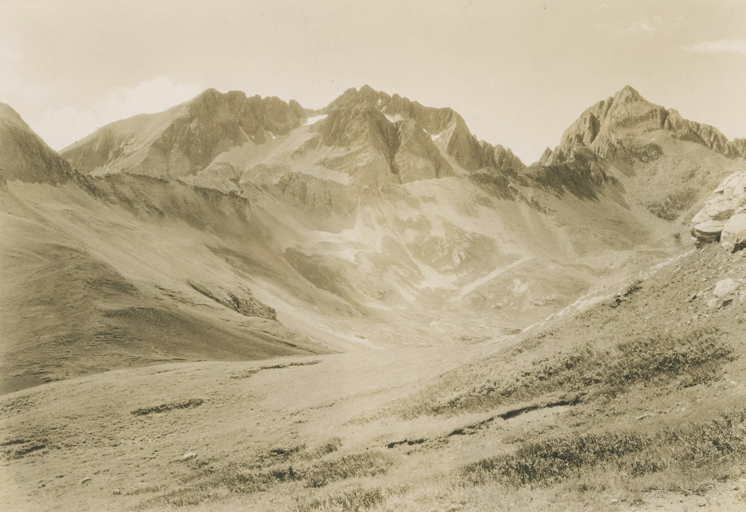 Untitled photo of alpine bowl, backed by several jagged peaks.
