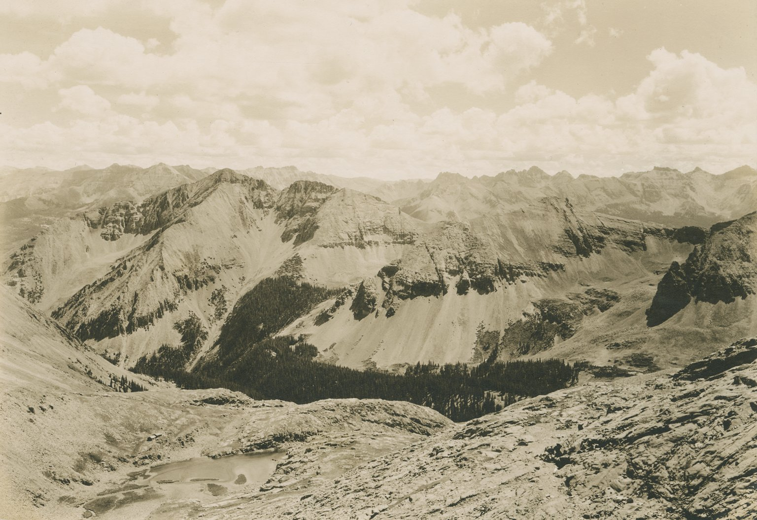 Untitled panoramic photo of several mountain ranges, with alpine lake and 2 small buildings in the middleground.
