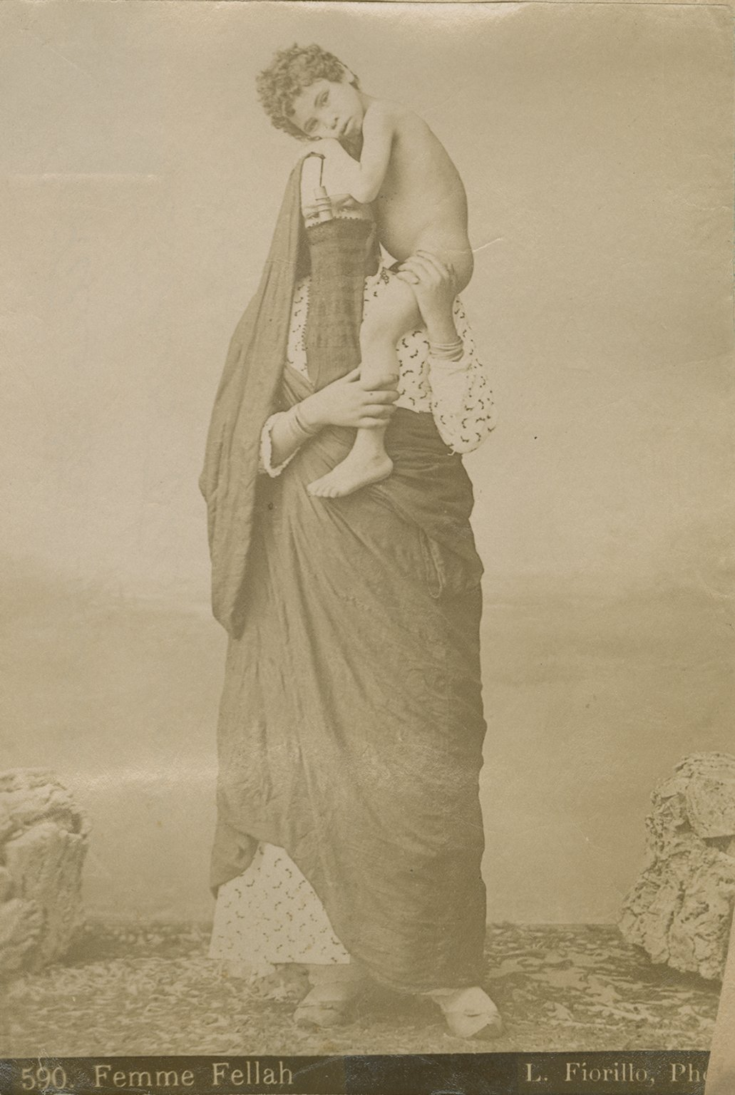 Veiled woman with young boy perched on her shoulder.