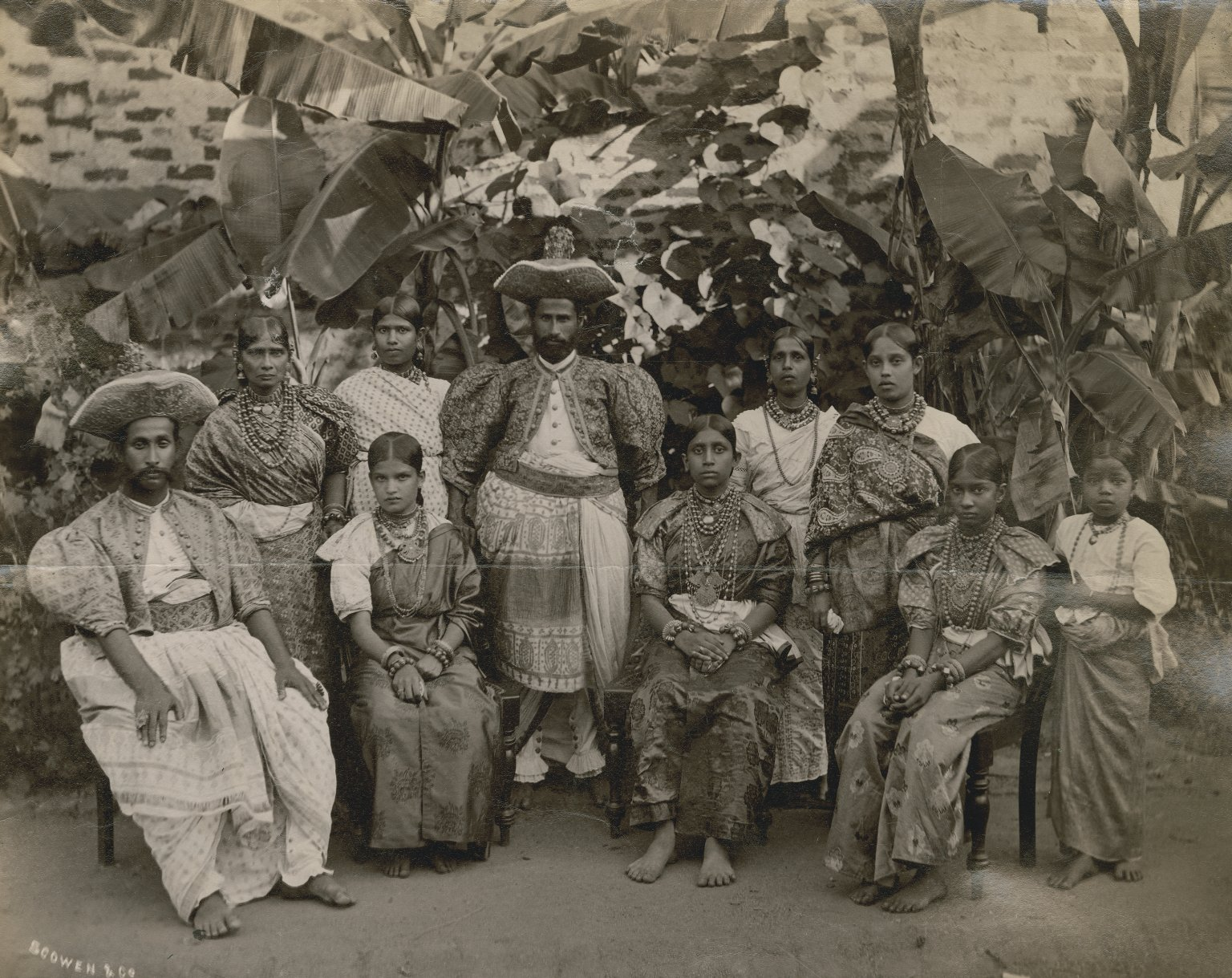Group portrait with some seated figures: 2 men, 8 women & children against a backdrop of tropical foliage.