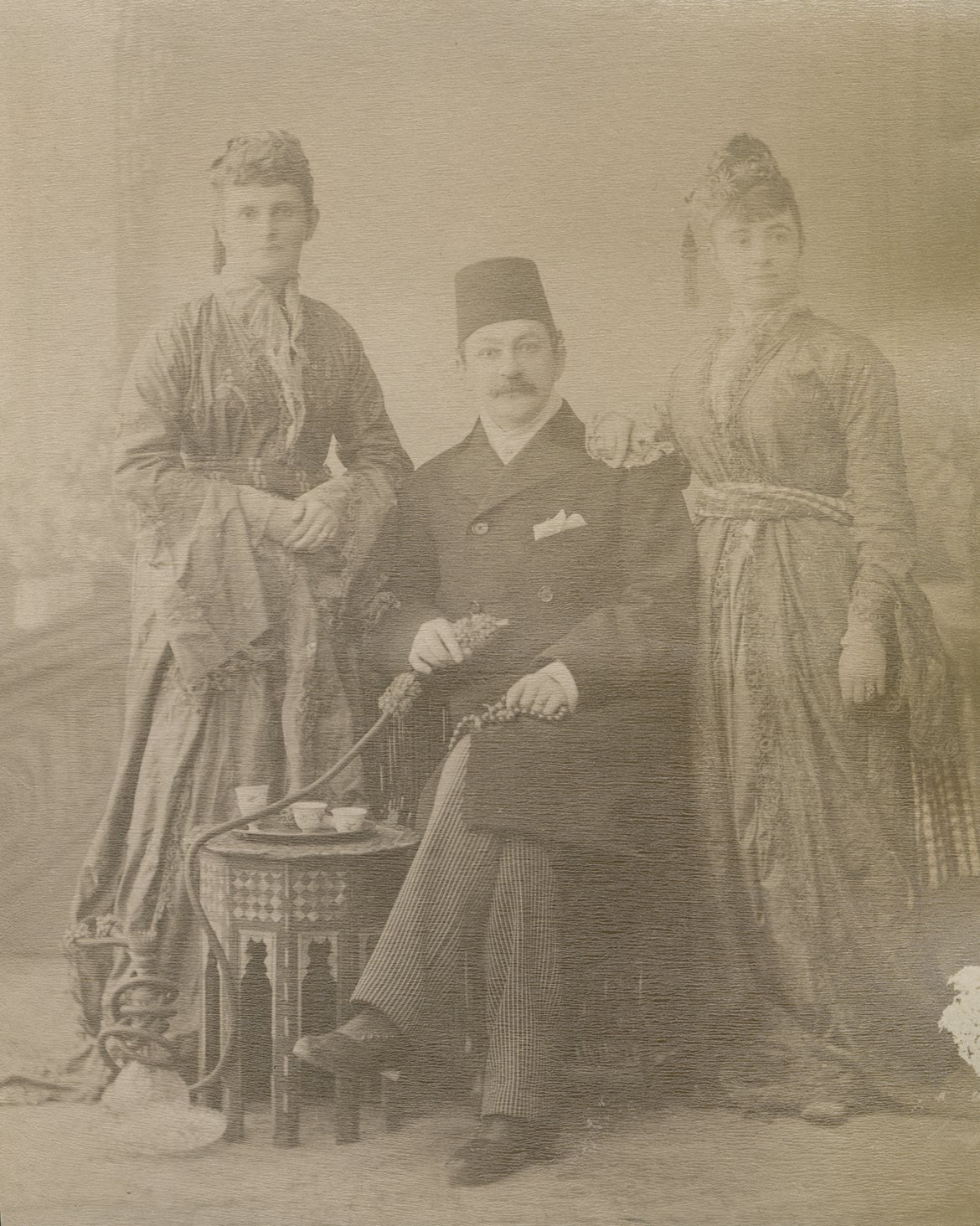 Man in fez and Western attire between two women in Western gowns